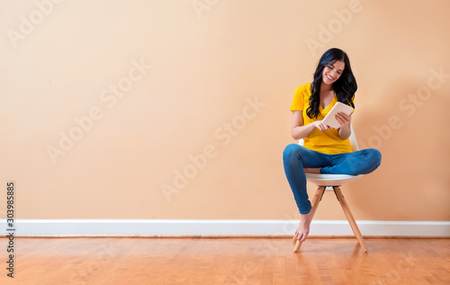 Cuadros en Lienzo Young woman using her tablet sitting in a chair