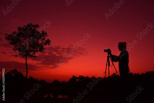 Photographer taking pictures outdoors, silhouette of a woman with camera over sunset