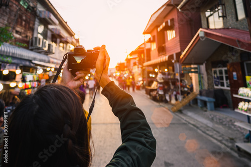 Young traveler taking photo with camera in walking street. Wallpaper Mural
