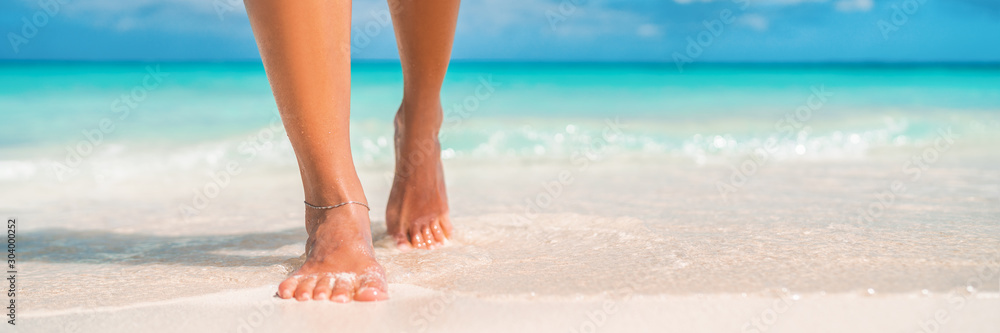Fototapeta Woman feet walking on caribbean beach barefoot closeup of foot coming out of water after swim banner panorama. Honeymoon travel vacation,