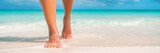 Fototapeta Fototapety z morzem do Twojej sypialni - Woman feet walking on caribbean beach barefoot closeup of foot coming out of water after swim banner panorama. Honeymoon travel vacation,
