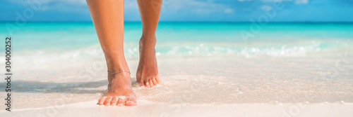 Fototapeta Woman feet walking on caribbean beach barefoot closeup of foot coming out of water after swim banner panorama. Honeymoon travel vacation, obraz