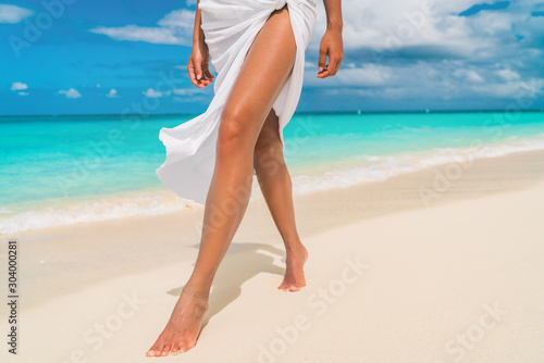 Fototapeta Elegant woman walking on Caribbean beach with slim smooth legs for skin care sun tan wearing cover-up sarong wrap beachwear skirt relaxing on tropical travel holiday
