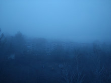 Gloomy City In The Fog. Thick Fog In The City. Apocalypse And Post-apocalypse. Empty Creepy Yard With Bare Trees In A Residential Area. An Empty Playground.