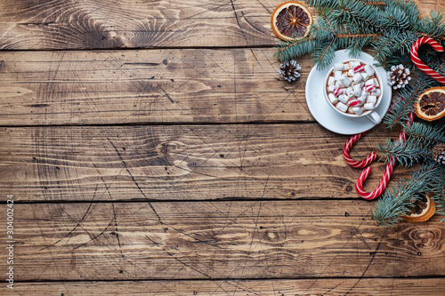 Spoed Foto op Canvas Chocolade A Cup of hot chocolate with marshmallows. Christmas tree and decorations, cane caramel and oranges nuts Wooden background copy space.