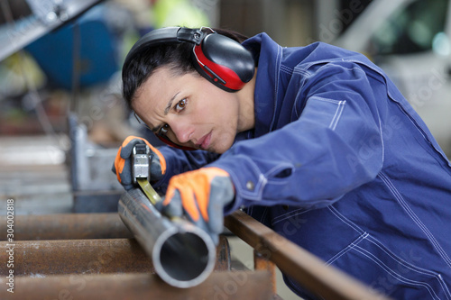 the worker measures and marks something on the pipes Wallpaper Mural