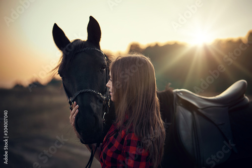Fototapeta lovely young girl in a plaid shirt hugs a black horse at sunset in the mountains obraz