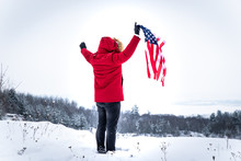 Man In Red Winter Coat Holding Usa Flag Outdoors In Snowy Weather