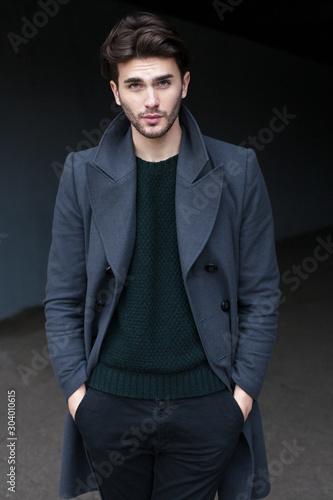 Outdoor portrait of handsome young man in coat Fototapete