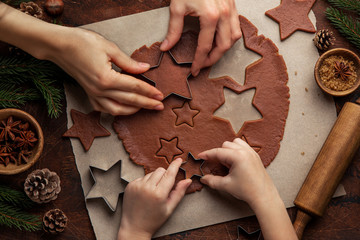 Christmas and New Year bakery. Close up of kids and female hands  cooking traditional gingerbread cookies.  Wooden kitchen table.