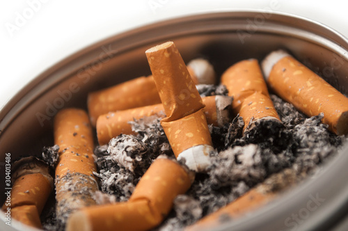 Closeup of metallic ashtray full of cigarettes habits on white background Wallpaper Mural
