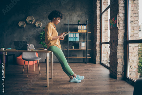 Photo Stands Akt Full size profile side photo of cool smart afro american girl entrepreneur use tablet work read start-up news wear yellow shirt green pants trousers in office loft