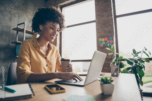 Obraz Profile side photo of charming smart afro american girl entrepreneur use computer work training company career development seminar sit table hold takeout mug hot beverage in loft office - fototapety do salonu