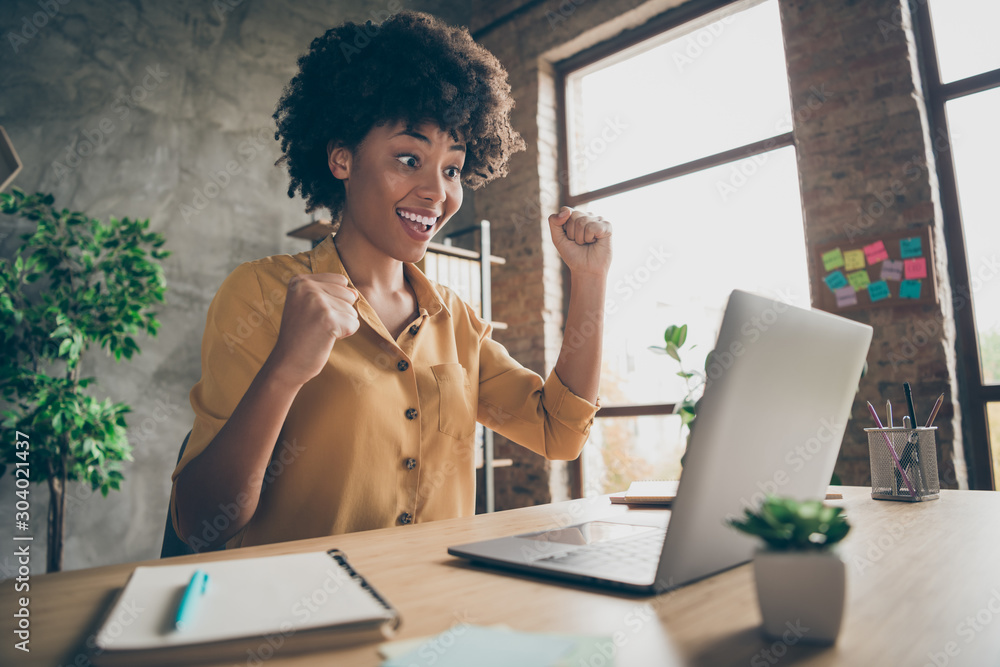 Fototapeta Photo of cheerful ecstatic mixed-race overjoyed entrepreneur in yellow shirt executive observing corporate income increased with notepad on desktop