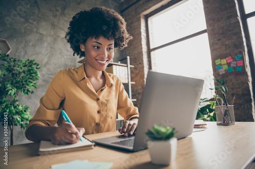Fotografía  Photo of cheerful joyful mixed-race woman in yellow shirt smiling toothily writi