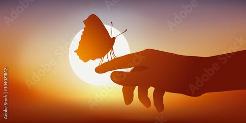 Fototapeta Concept de la légèreté et de la fragilité, avec la silhouette d'un papillon posé sur une main vu en contre jour face à un coucher de soleil