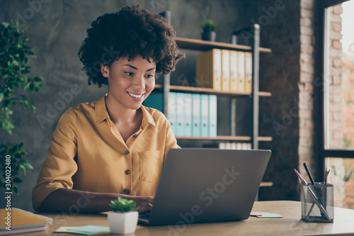 Fototapeta Photo of cheerful positive mixed-race girl smiling toothily working on presentation about her corporation using laptop on desktop obraz na płótnie