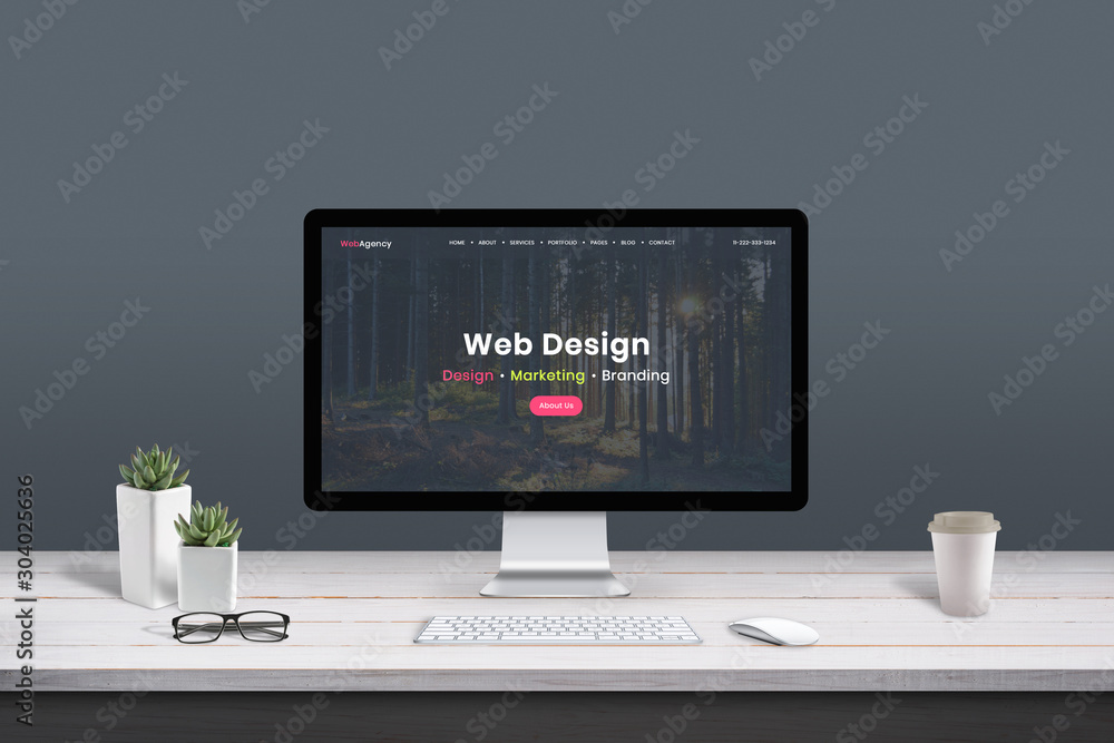 Fototapeta Web design studio concept. Work desk with computer display and modern design web agency page.