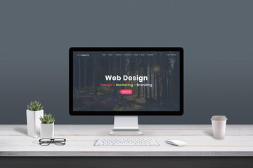 Web design studio concept. Work desk with computer display and modern design web agency page.