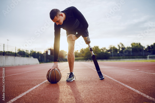 Fotografía  Full length of sporty caucasian handicapped man in sportswear and artificial leg dribble the ball while standing on racetrack