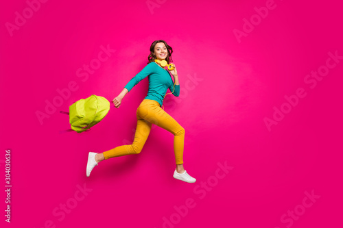 Obraz Full length body size side profile photo of cheerful positive nice pretty cute youngster wearing yellow pants trousers smiling toothily isolated pink vibrant color background - fototapety do salonu
