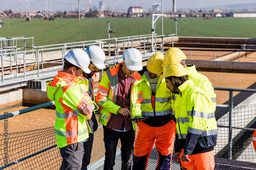 Valokuva  Engineers and workers assesing wastewater plant