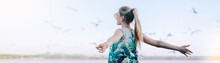 Girl In A Dress Against The Sky And Flying Birds Near The Water. Young Woman Spread Her Arms And Stands In A Free Pose. Banner