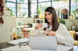 Attractive caucasian elegant brunette sitting in cafe, drinking coffee. On table is laptop.