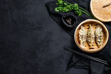 Korean Dumplings In A Traditional Bamboo Steamer. Top View. Space For Text. Rustic Old Vintage Black Background