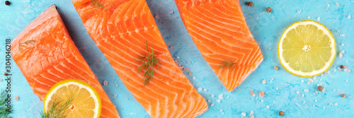 Canvas Print Slices of salmon with lemon and dill panorama, a top shot with salt and pepper on a blue background