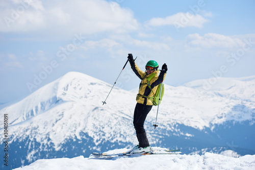 Fotomural Sportsman skier in helmet and goggles with backpack standing on skis holding ski poles in raised arms, in deep white snow on copy space background of bright blue sky and beautiful mountain view