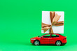 canvas print picture - Red toy model car with present gift box on the top, green background