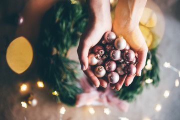 Girl making a handmade christmas wreath. Idea for the festive decoration of the interior. Christmas mood. Close up hand with christmas ball.