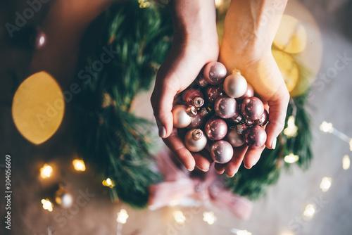 Obraz Girl making a handmade christmas wreath. Idea for the festive decoration of the interior. Christmas mood. Close up hand with christmas ball. - fototapety do salonu