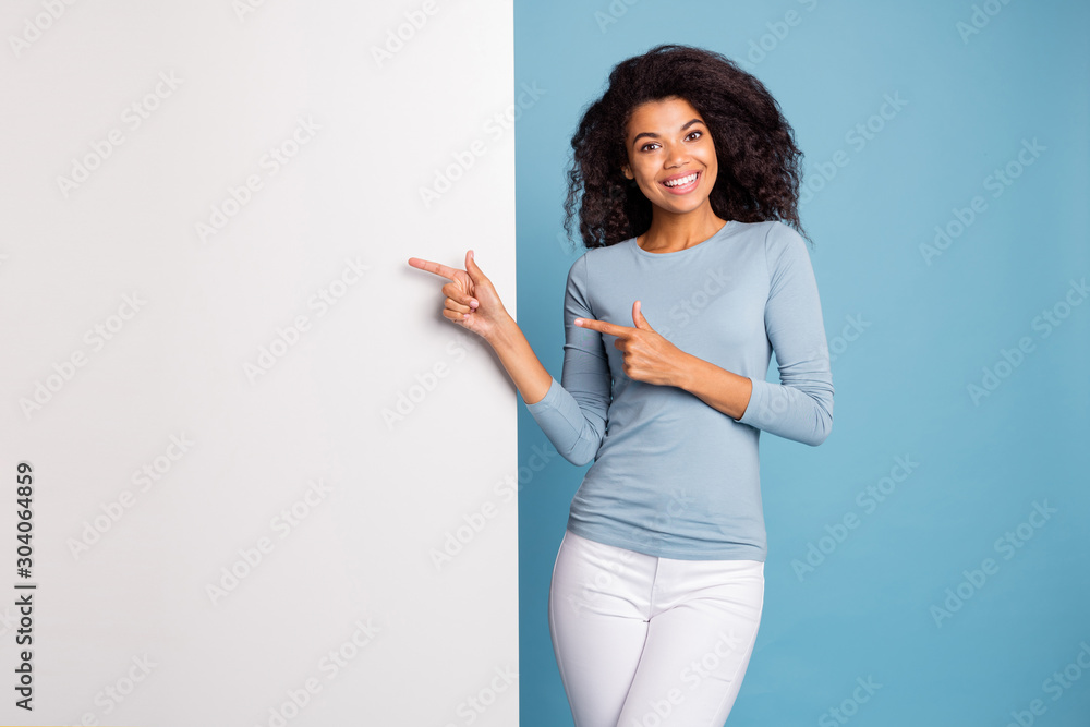 Fototapety, obrazy: Photo of brunette haired cheerful positive cute nice curly wavy girl pointing at empty white banner space in pants trousers blue sweater smiling toothily isolated pastel color background