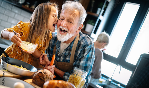 Fototapeta Grandfather and his grandchildren spendig happy fun time in kitchen obraz