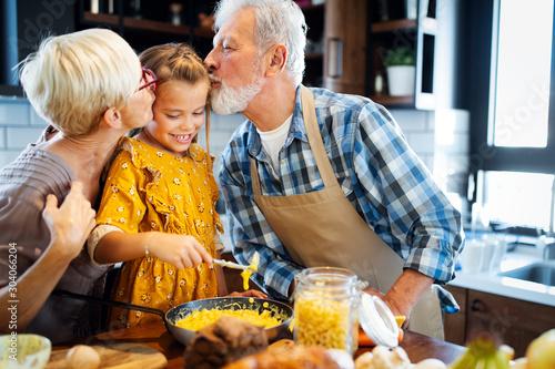 Foto op Aluminium Kruidenierswinkel Happy grandparents with grandchildren making breakfast in kitchen