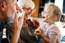 Happy Grandparents Playing With Their Little Cute Granddaughter
