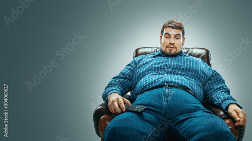 Portrait of fat caucasian man wearing jeanse and whirt sitting in a brown armchair isolated on gradient grey background Fototapeta