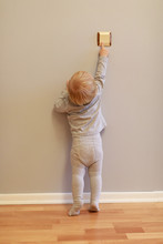 Little Blonde Baby Girl Near The Grey Wall Is Trying To Turn Off The Light By Reaching The Switch Stretching  On Her Foot Toes