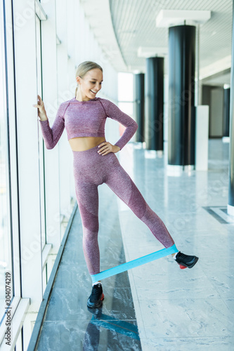 Fotografía Slim woman doing squats with fitness loop band at gym