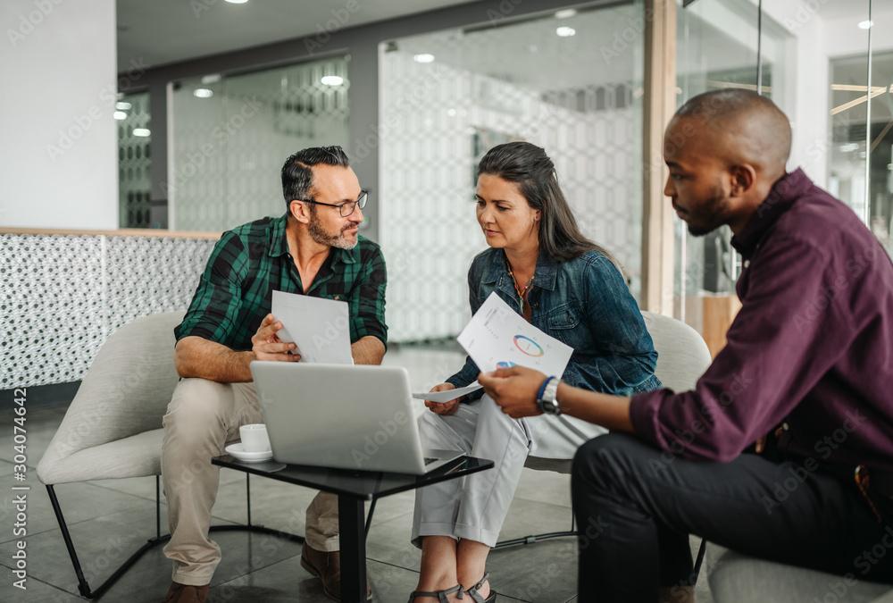Fototapeta Casual meeting of diverse business team analyzing financial data