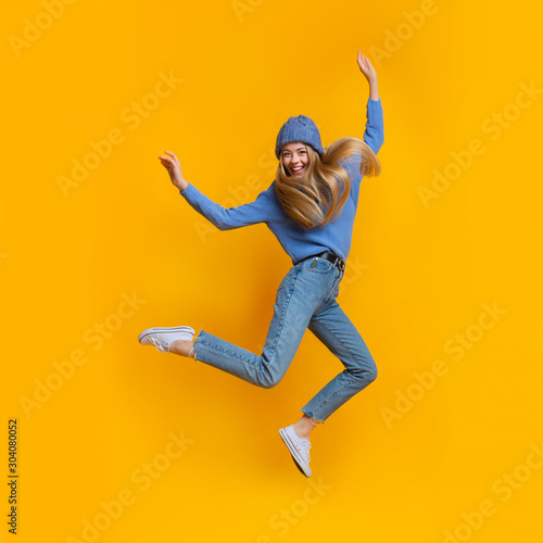 Breezy girl in blue jumping in the air
