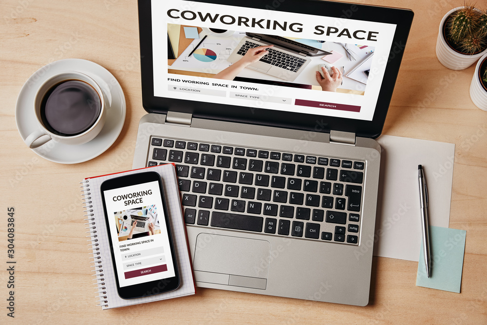 Fototapeta Coworking space concept on laptop and smartphone screen