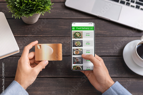 Man using credit card and smartphone with food delivery application Fototapet