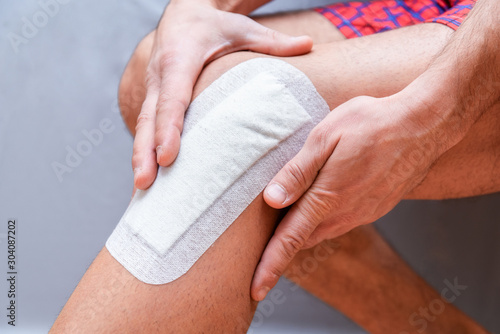 Fotomural  medical plaster is glued to the knee of the male leg after surgery
