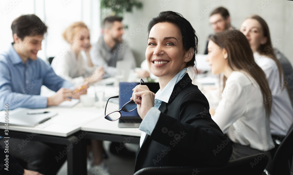 Fototapeta Female top manager smiling to camera at meeting