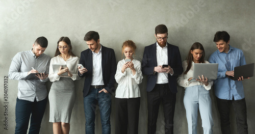 Cuadros en Lienzo  Businesspeople with gadgets standing in row over grey wall