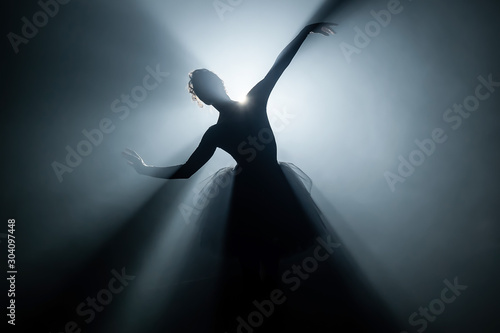 Solo performance by ballerina in tutu dress against backdrop of luminous neon spotlight in theater Wallpaper Mural