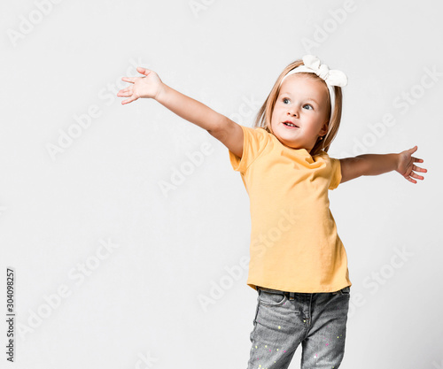 Pretty little kid baby girl in yellow t-shirt is singing with her hands up sprea Wallpaper Mural